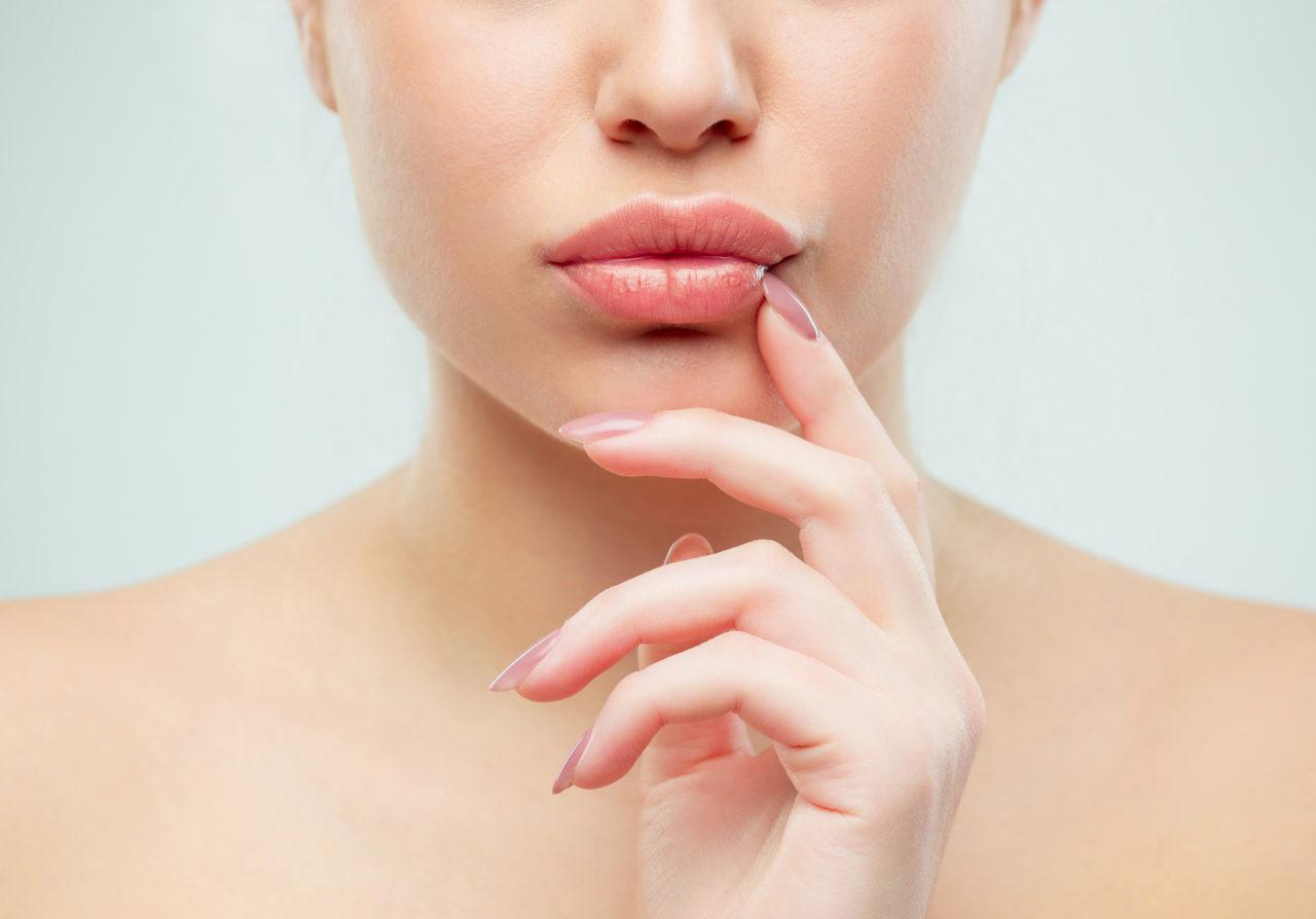 Kobieta dotyka swoich ust