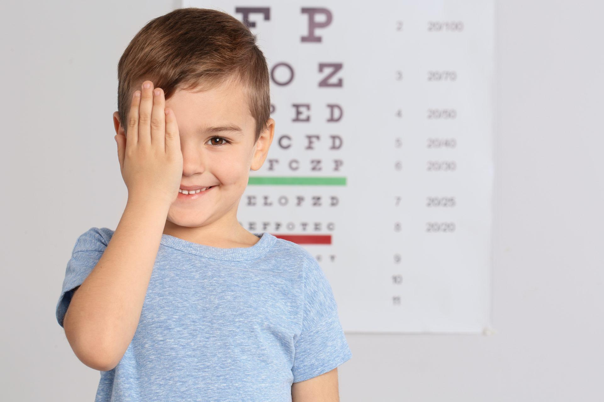 Chłopiec u okulisty zasłania jedno oko