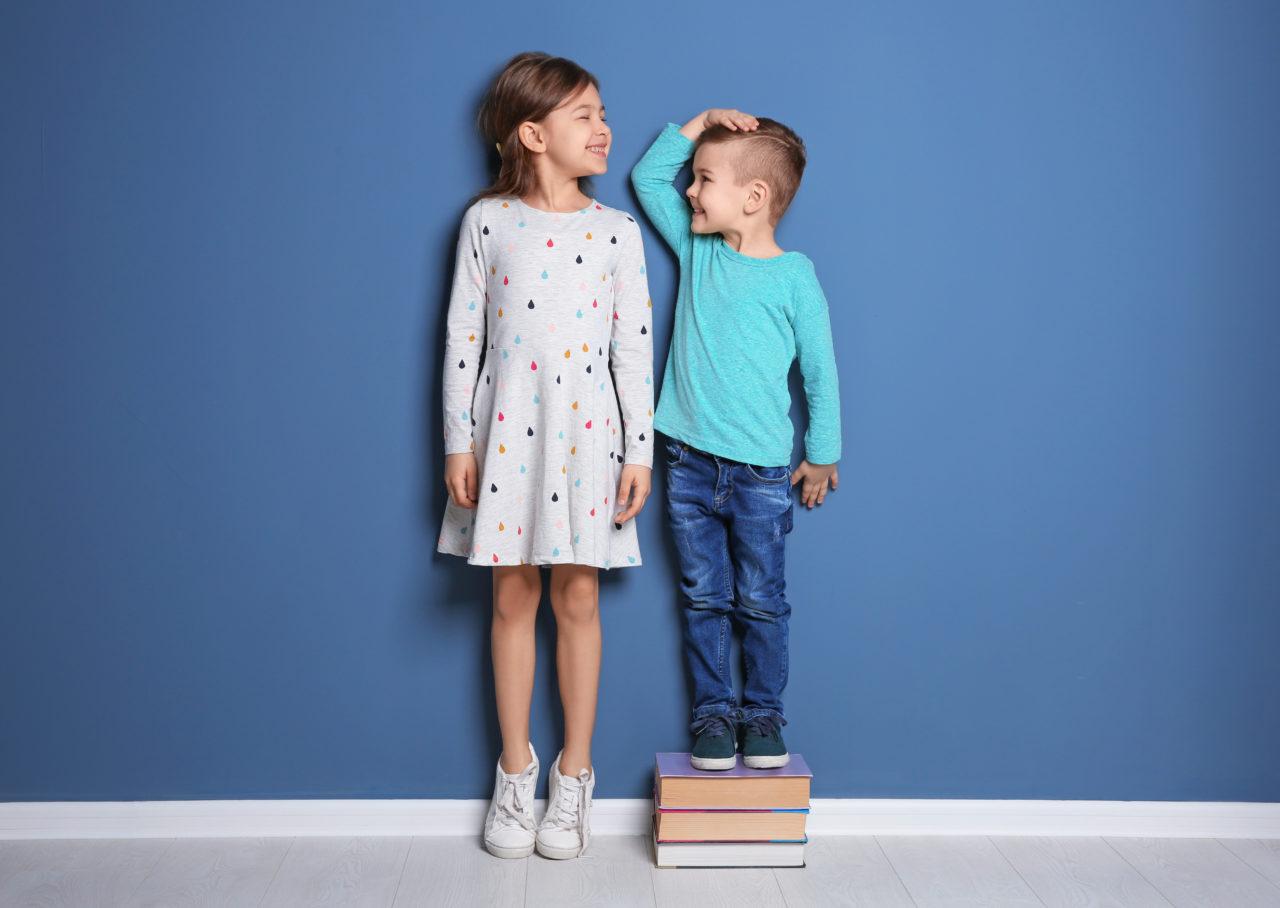 Dziewczynka i chłopczyk mierzą swój wzrost
