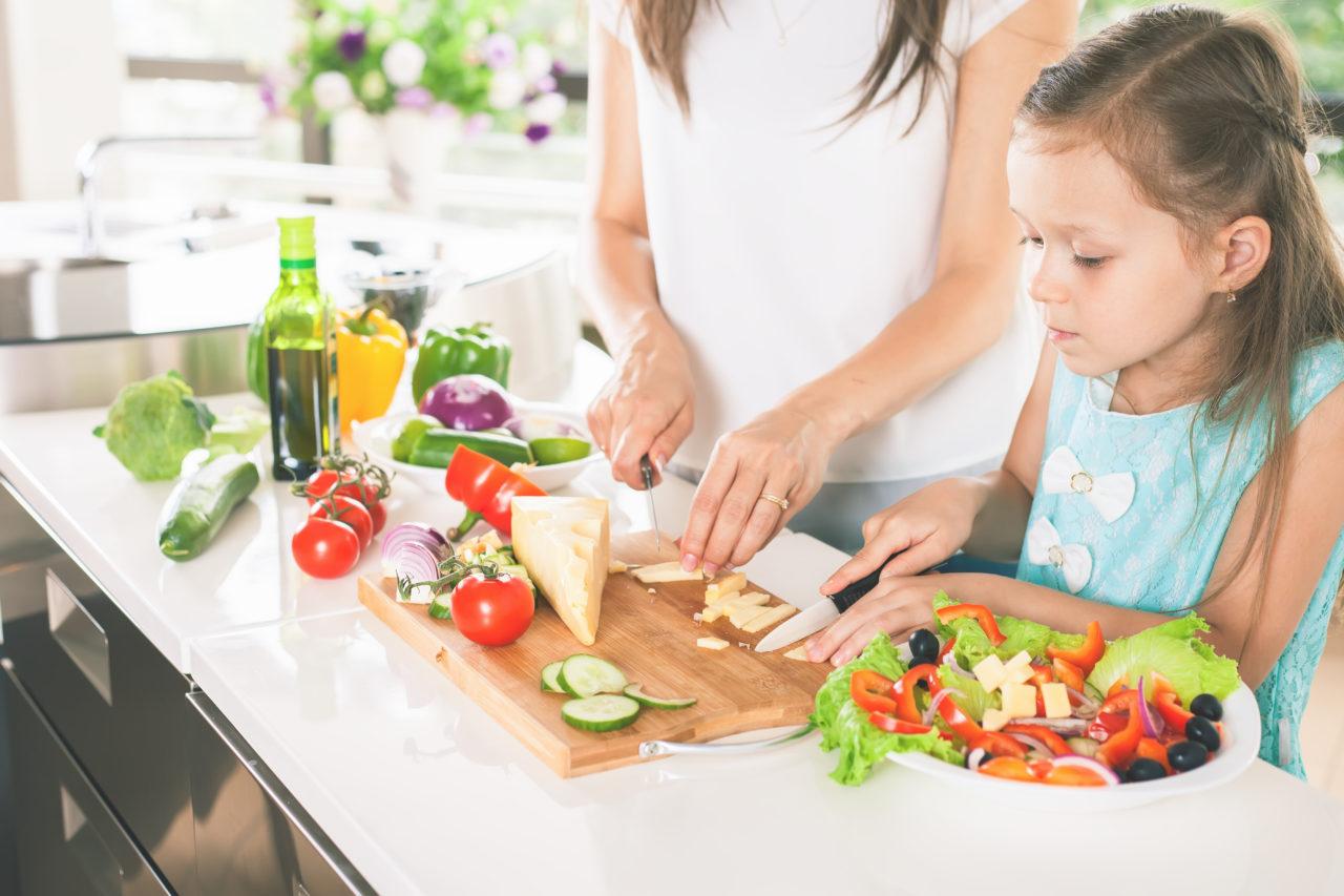 Dziewczynka pomaga mamie przy przygotowywaniu zdrowego posiłku