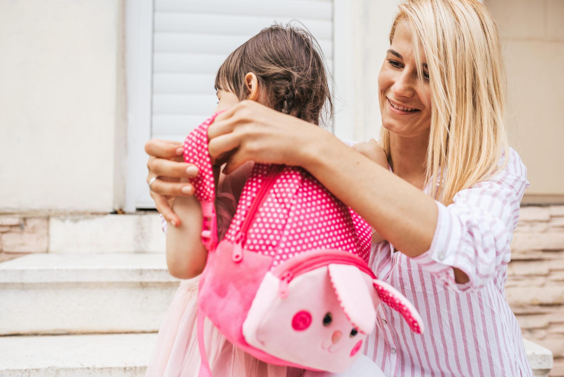 Mama zakłada córeczce plecak