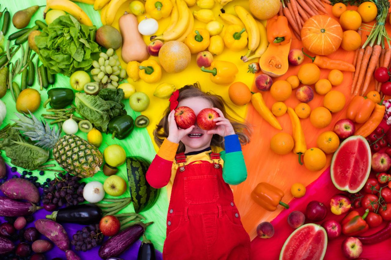 Dziewczynka w otoczeniu warzyw i owoców