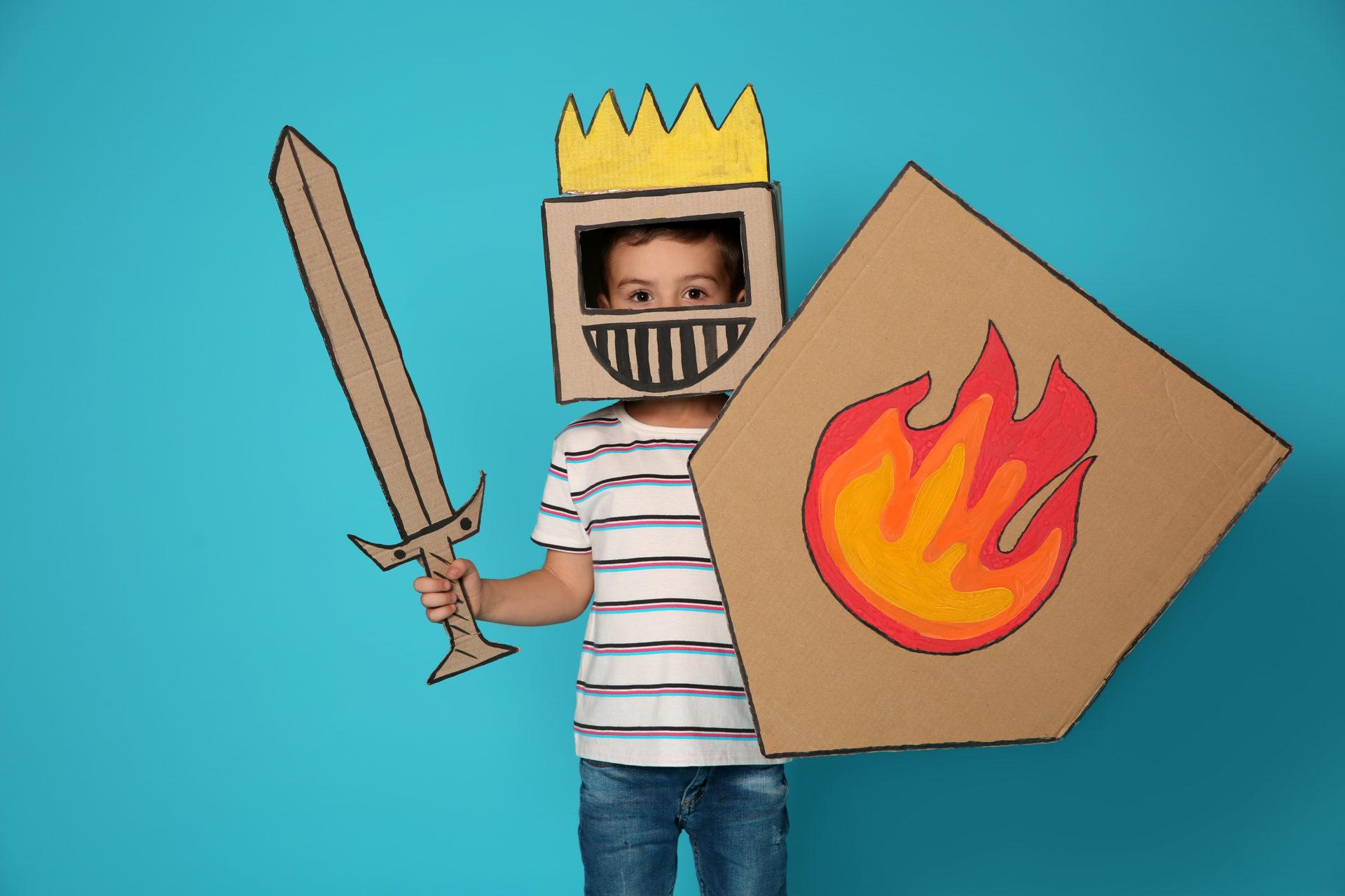 Chłopiec w kartonowym stroju rycerza z tarczą