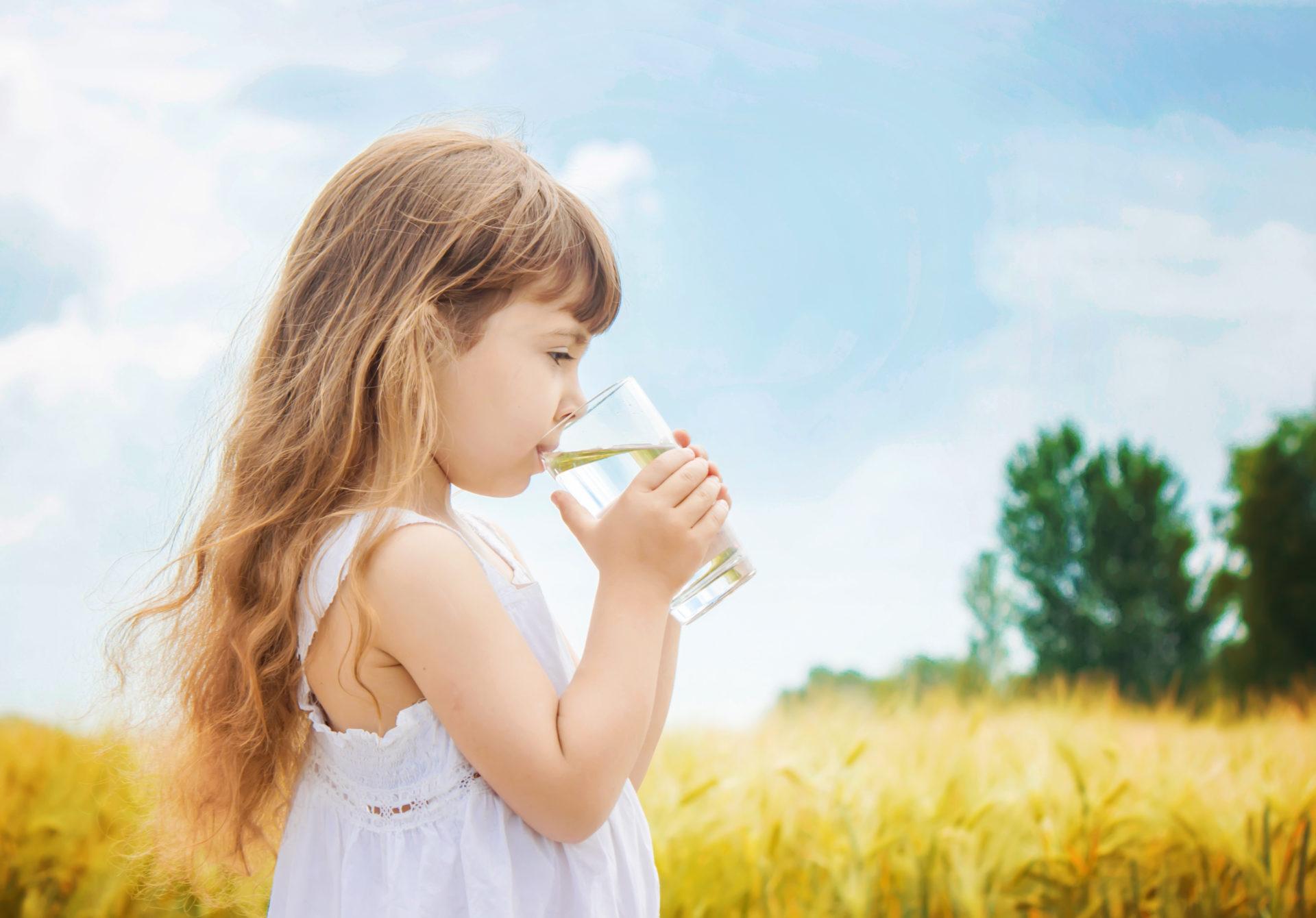 Dziewczynka ze szklanką wody, w tle polana