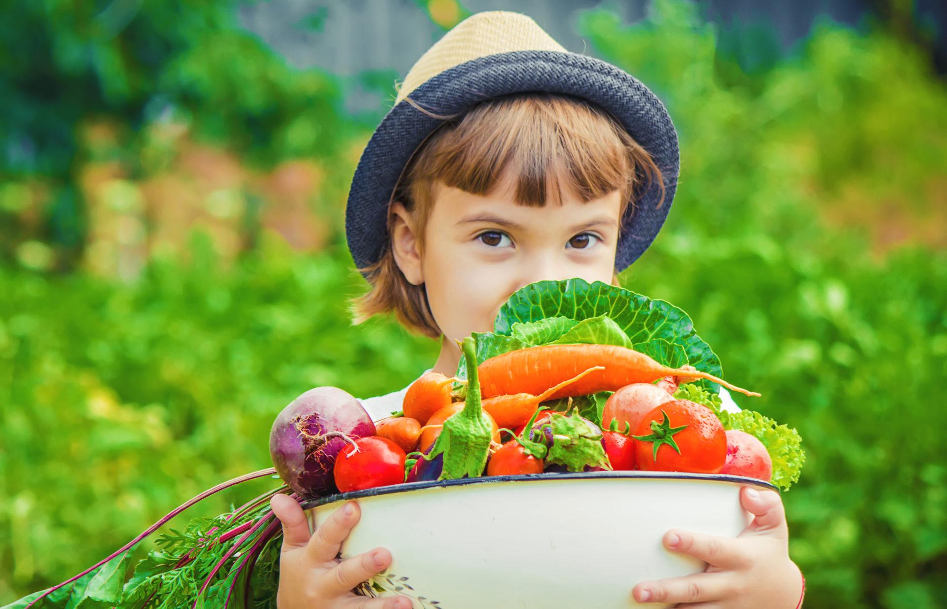 Dziewczynka ze świeżo zebranymi warzywami