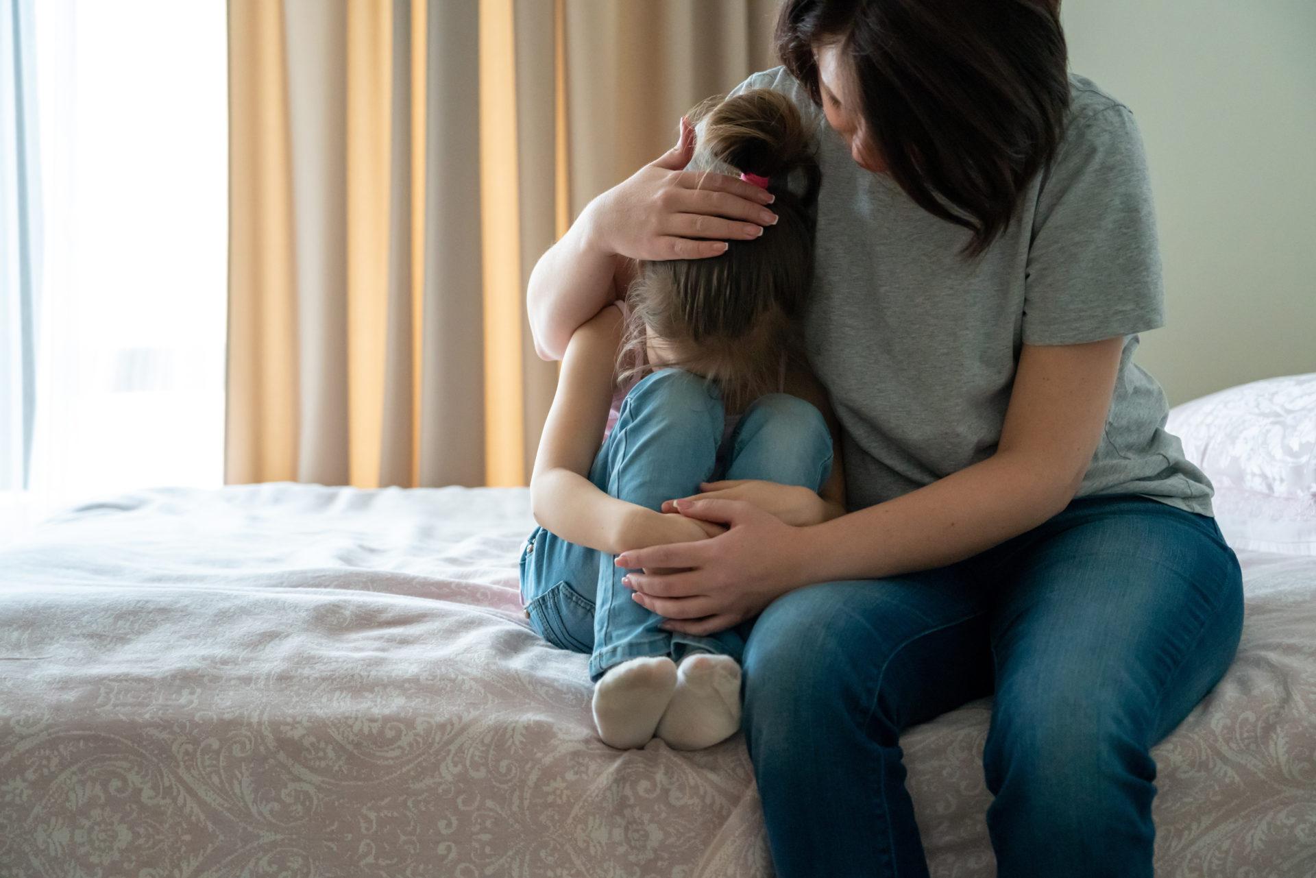 Mama przytula smutną córeczkę, oferując wsparcie