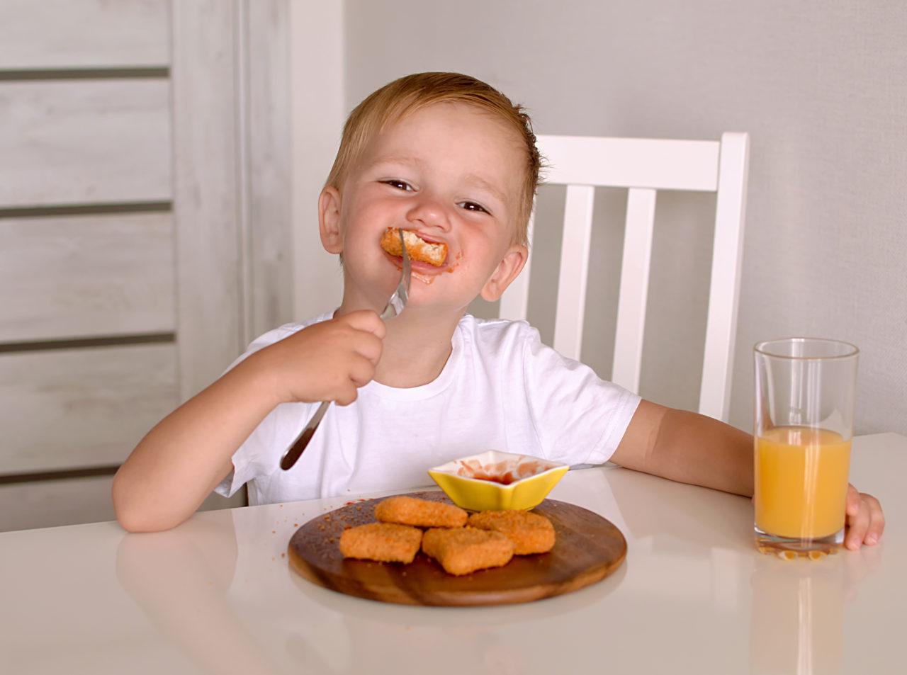 Chłopiec zjada domowy obiad - nuggetsy z kurczaka