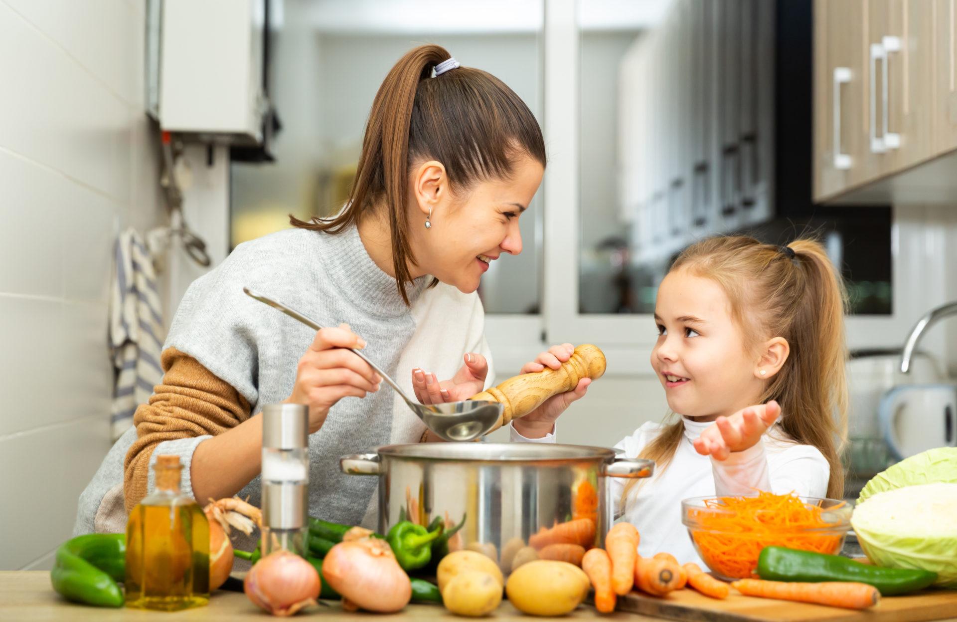 Mama z córeczką kosztują zupę