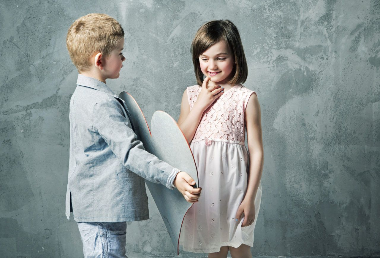Chłopiec podtrzymuje lustro w którym przegląda sięzadowolona z siebie dziewczynka