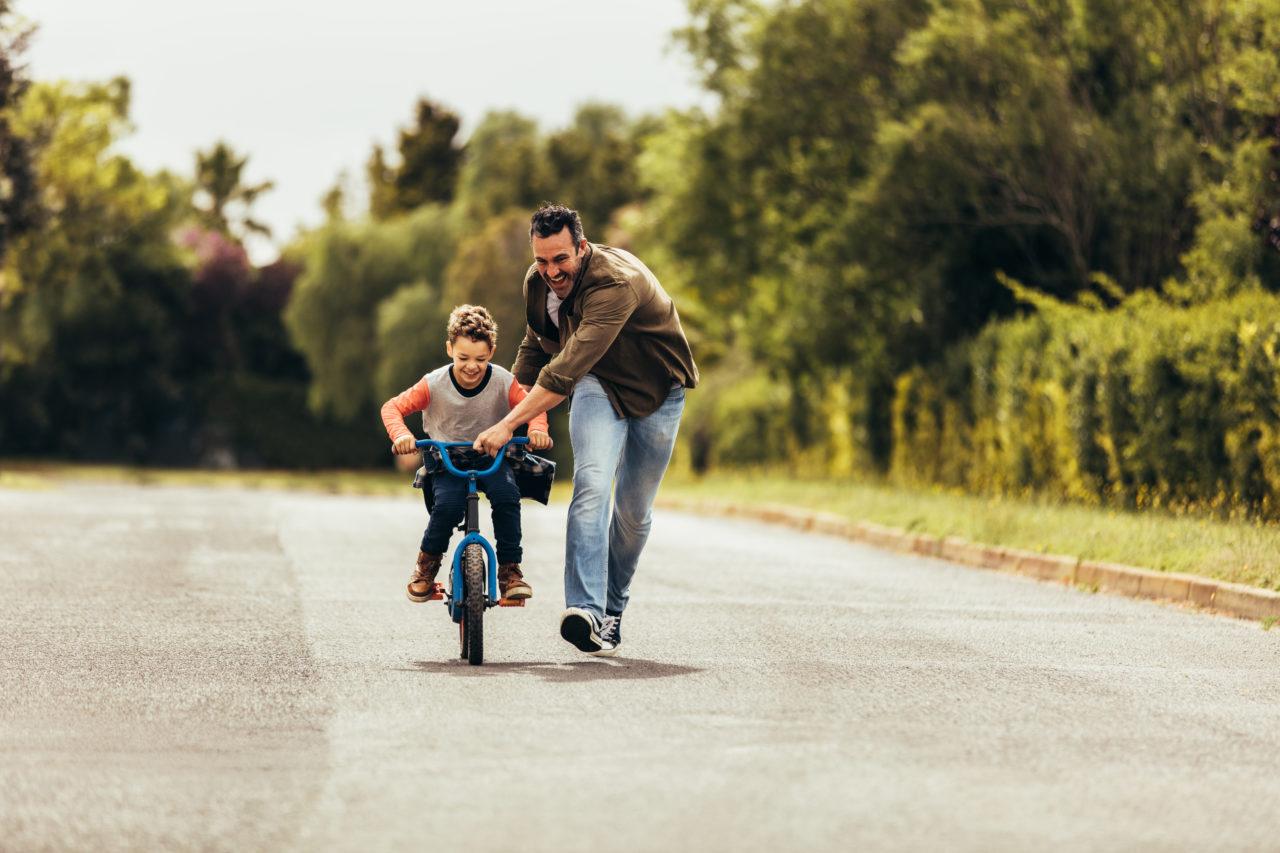 Tata uczy syna jazdy na rowerze