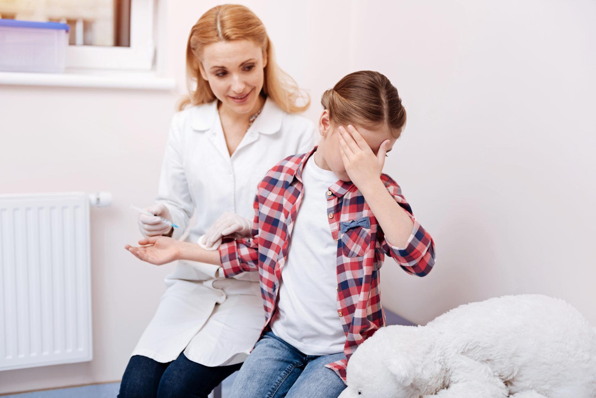 Przestraszona dziewczynka zasłania twarz podczas szczepienia