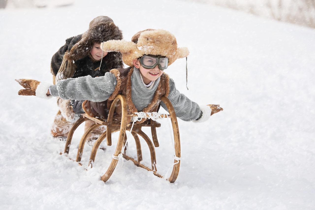 Zima. Dzieci zjeżdżają na sankach.