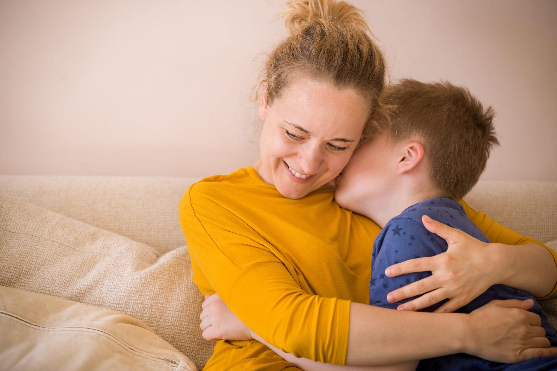 Chłopiec przytula się do uśmiechniętej mamy