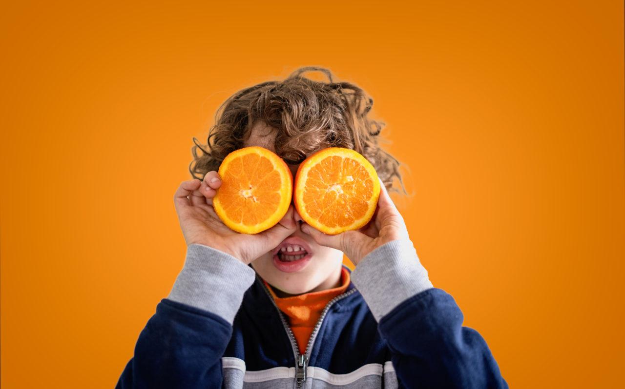 Chłopiec trzymający dwie połówki pomarańczy