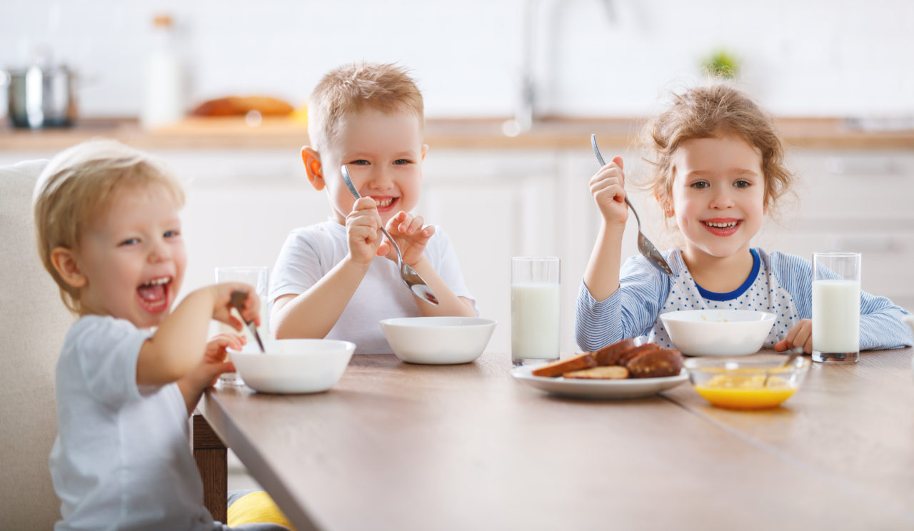 Roześmiane dzieci zjadają śniadanie