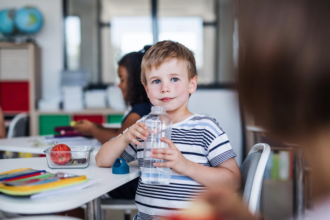 Chłopiec siedzi w szkole i pije wodę