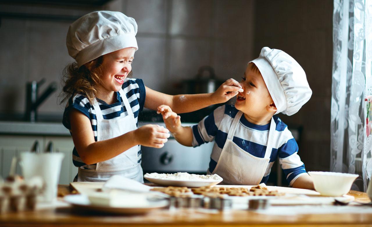 Roześmiane dzieci wspólnie pieką ciasteczka